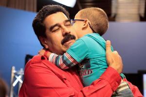 Maduro abbraccia un bambino curato grazie alla Misión Milagro